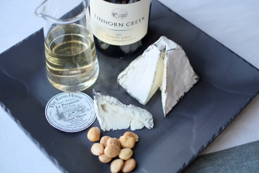 A slate square plate with almonds, Pinot Gris in a glass as well as in the bottle, and La Pyramide with a wedge cut out to showcase the cheese's interior.